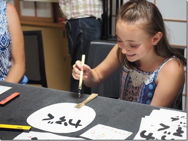 和様の書道体験をする外国人の子供の画像
